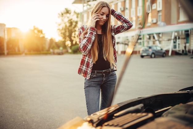 Avería del coche, mujer triste contra el capó abierto
