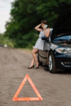 Avería del coche, señal de parada de emergencia, mujer pidiendo ayuda
