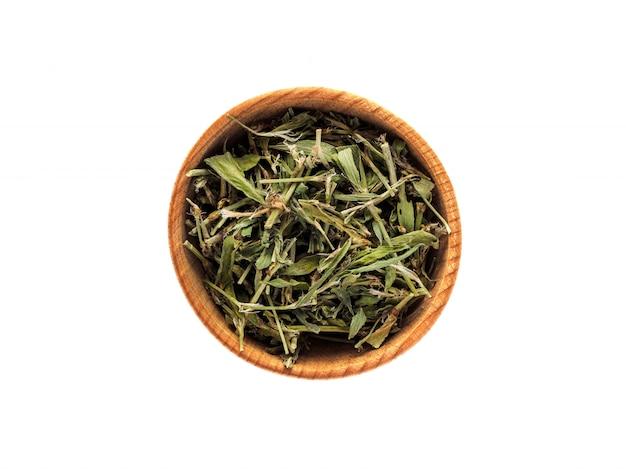 Aviculare highlander seco o knotweed en copa de madera sobre mesa blanca