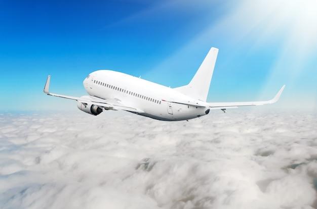 El avión blanco está subiendo alturas de vuelo, en la parte inferior hay nubes nubladas.