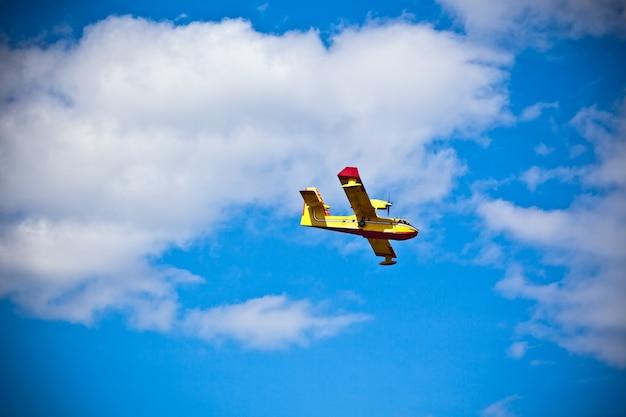 Avión de bombero amarillo brillante en un cielo azul. tiro horizontal