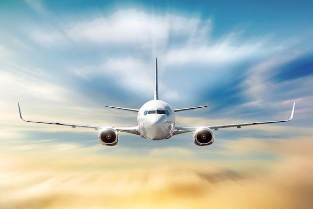 Avión con efecto de desenfoque de movimiento está volando en nubes naranjas al atardecer. concepto aviación transporte aéreo