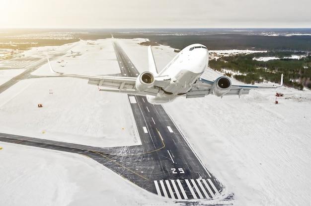 El avión es una vista alta del nivel de vuelo de subida en el aire, el aeropuerto de invierno de la pista, ciudad, nieve, bosques y carreteras.