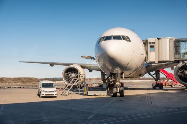 Avión grande de pasajeros estacionado en la pista con conexión a los pasillos.