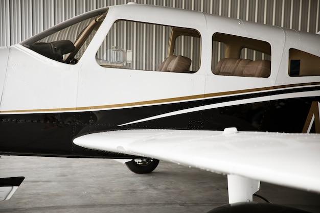 Avión de hélice delantera estacionado en un hangar