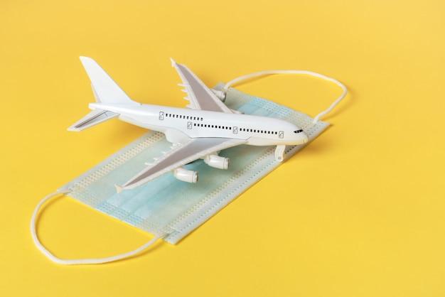 Un avión de juguete blanco se encuentra sobre una máscara protectora contra la enfermedad. sobre un fondo amarillo.