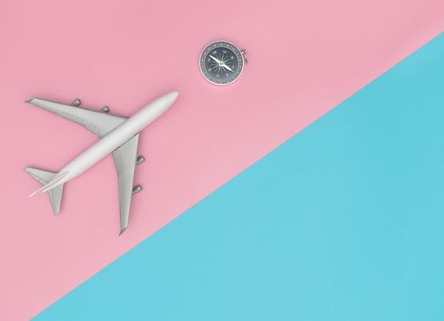 Avión de juguete con brújula para el concepto de viaje chic colorido, con pin y azul pastel copia espacio.