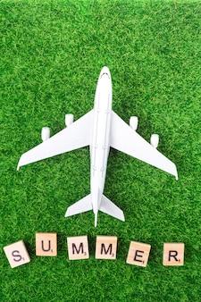 Avión de juguete y letras sobre hierba.