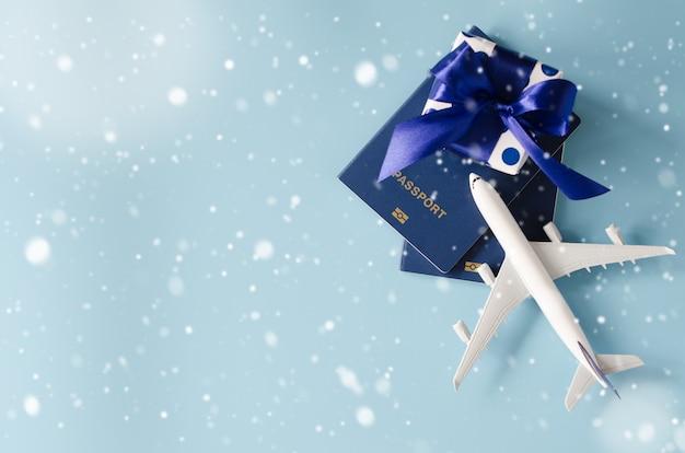 Avión de juguete con pasaportes y caja de regalo sobre fondo azul.