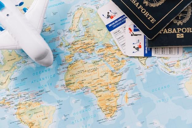 Avión de juguete; pasaportes y franquicias de equipaje en el mapa.