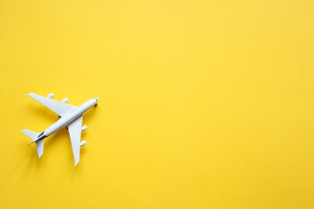 Avión de juguete sobre un fondo amarillo pastel