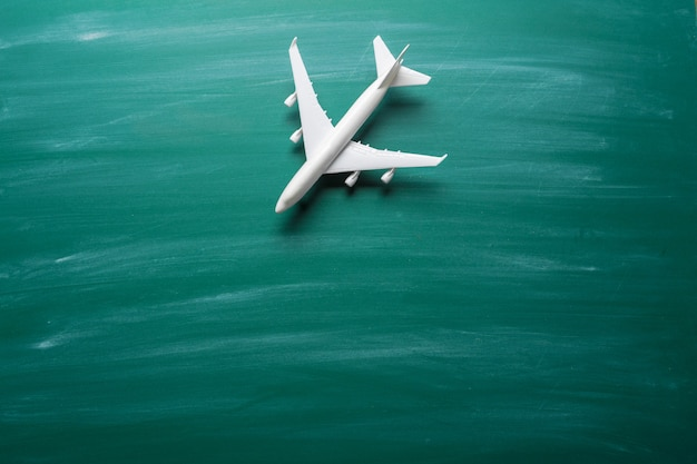 Avión de juguete sobre fondo de pizarra