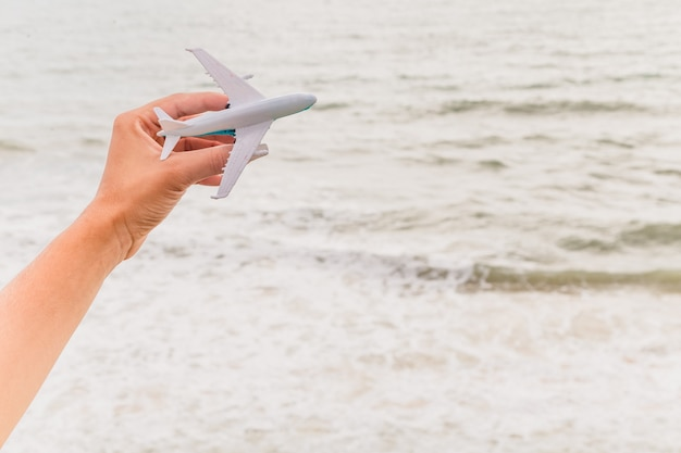 Avión de juguete volando, mostrando la playa y el cielo, representando viajes y turismo