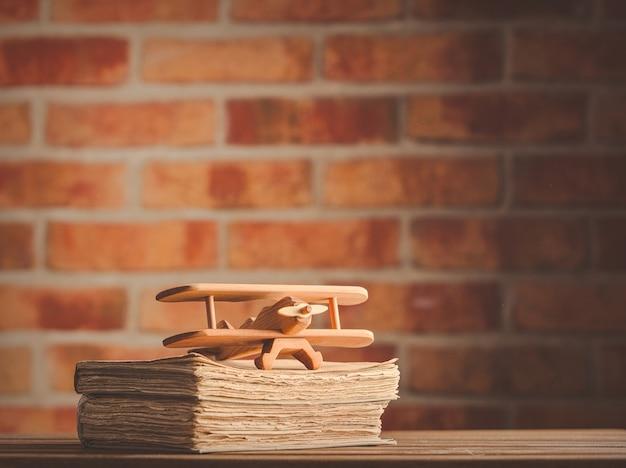 Avión de madera de juguete y libros antiguos.
