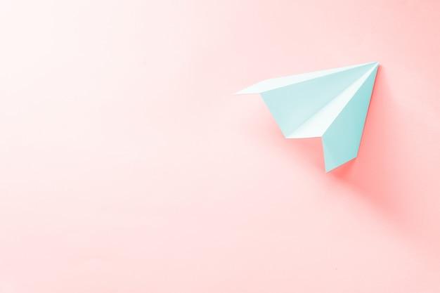 Avión de papel azul pálido sobre coral