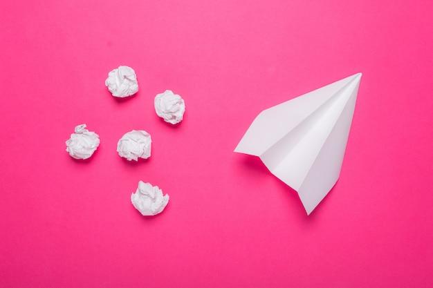 Avión de papel blanco y bolas de papel arrugado sobre un fondo rosa