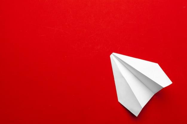 Avión de papel blanco sobre un fondo rojo.