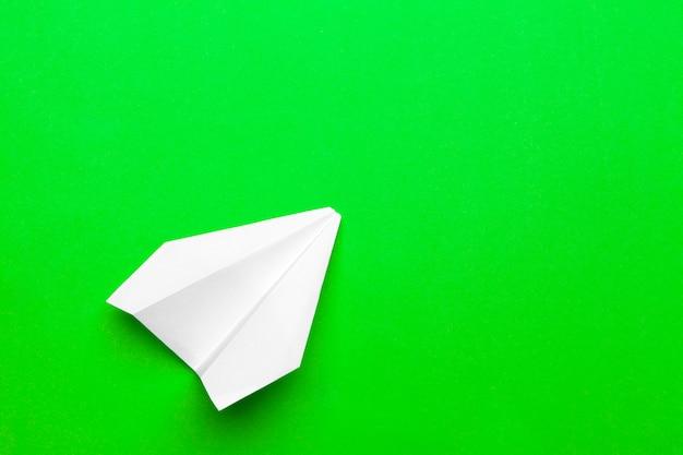Avión de papel blanco sobre un papel verde