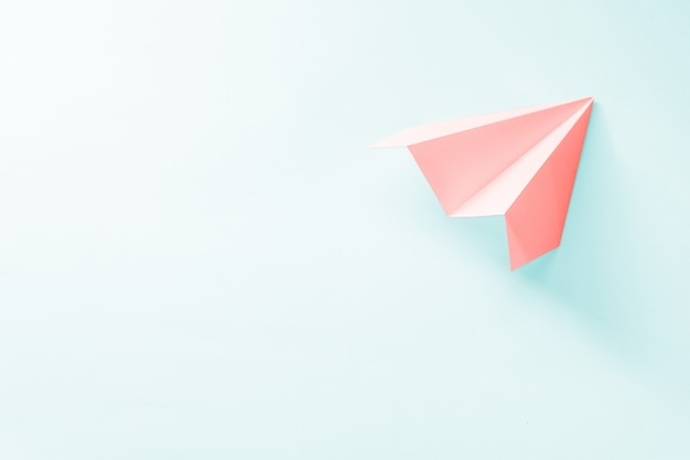 Avión de papel coral sobre un fondo azul pálido. concepto de color de moda 2019