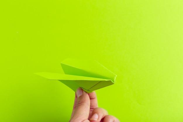 Avión de papel en el fondo brillante que se sostiene en mano humana. concepto de viajes y turismo.