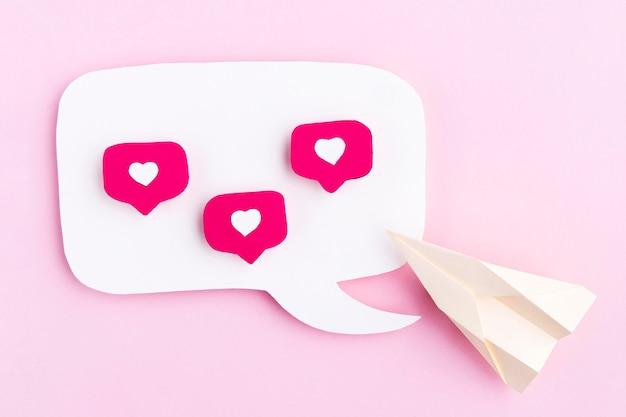 Avión de papel con iconos de corazón