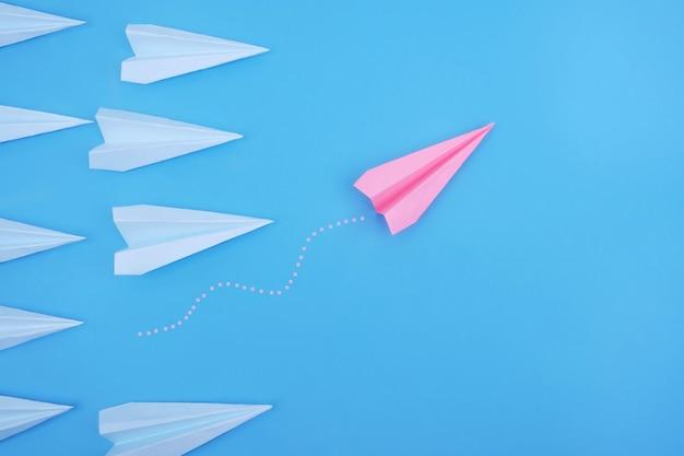 El avión de papel rosa es diferente de los demás sobre un fondo azul.