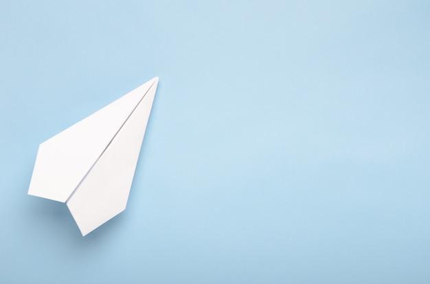 Avión de papel sobre un fondo azul.