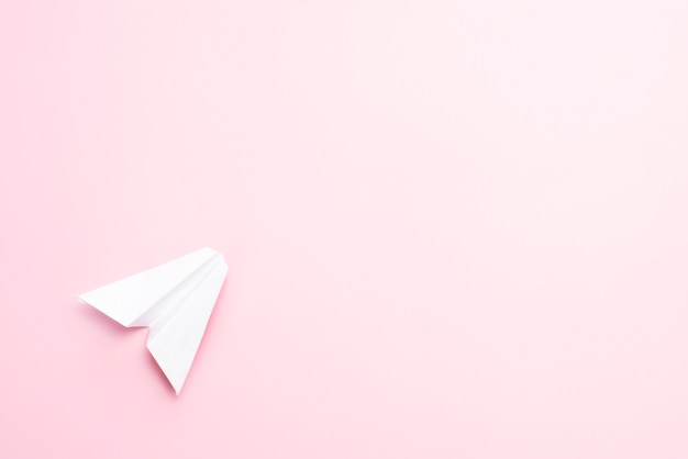Avión de papel sobre un fondo rosa.