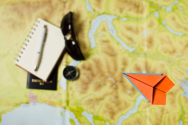 Avion de papel vista superior con accesorios de viaje.