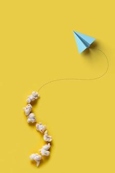 Avión de papel volando, palomitas de maíz y líneas sobre fondo amarillo. concepto de emprendimiento, evolución y recorrido empresarial.