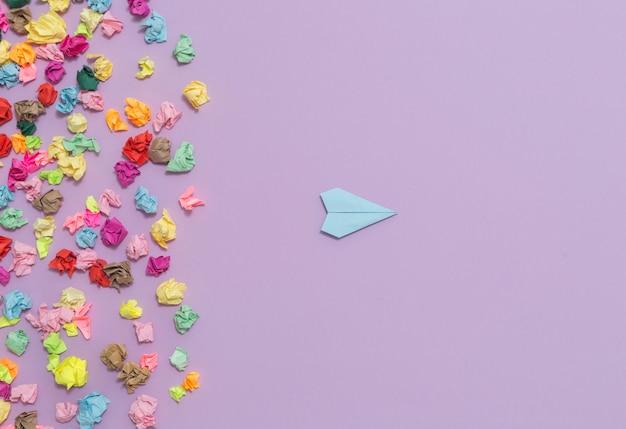 Avión de papel vuela lejos de pegatinas arrugadas