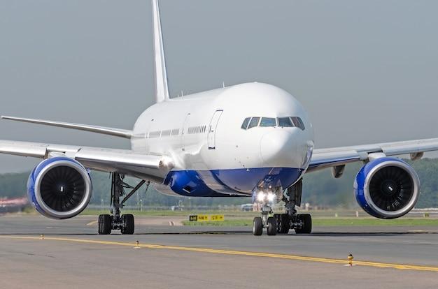 Avión de pasajeros blanco monta la pista de rodaje en el aeropuerto.
