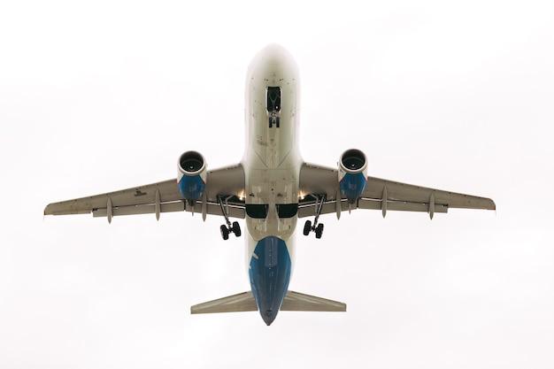 Avión de pasajeros blanco vuela contra el cielo