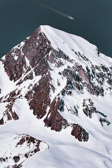 Avión de pasajeros con estela pasando por encima del pico de la montaña nevada