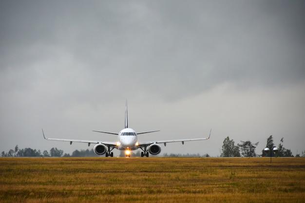 Un avión de pasajeros con luces encendidas viajará a la pista en el campo del aeropuerto en la noche bajo la lluvia