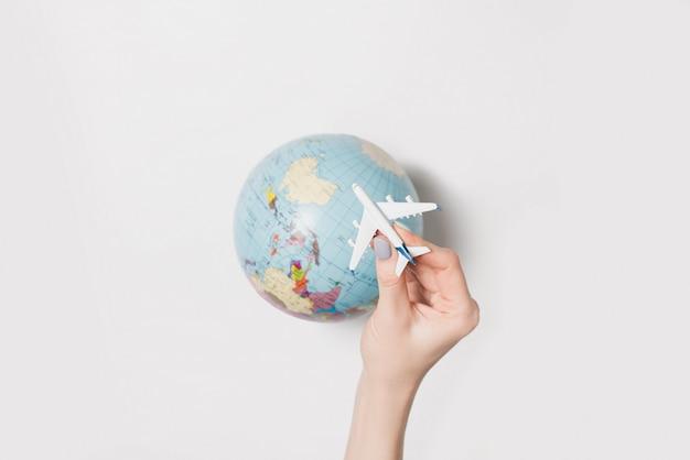 Avión de pasajeros en una mano femenina y globo terráqueo. concepto de vuelo