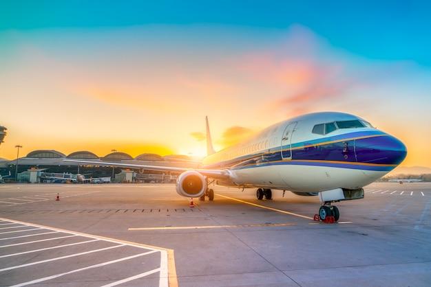 Avión de pasajeros en la pista y el delantal del aeropuerto