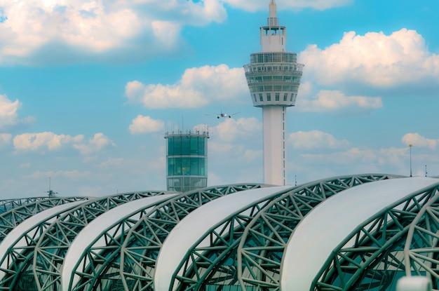 Avión de pasajeros volando por encima del edificio del aeropuerto edificio del aeropuerto y torre de control del tráfico aéreo