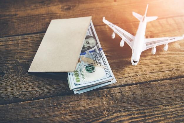 Avión y pasaporte con dinero en el escritorio