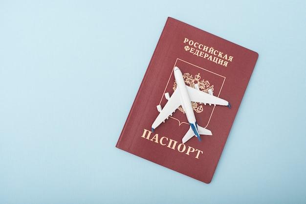 Avión en el pasaporte ruso. concepto de viaje. fondo azul