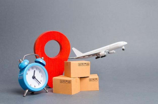 Avión y pila de cajas de cartón, pin de posición rojo y despertador azul.