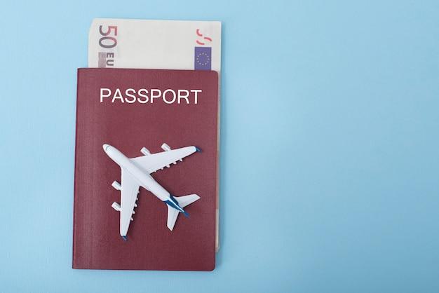 Avión en la portada del pasaporte. euro. concepto de viaje. fondo azul