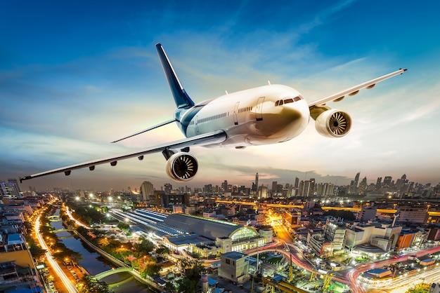 Avión de transporte sobrevolando la ciudad en la hermosa puesta de sol