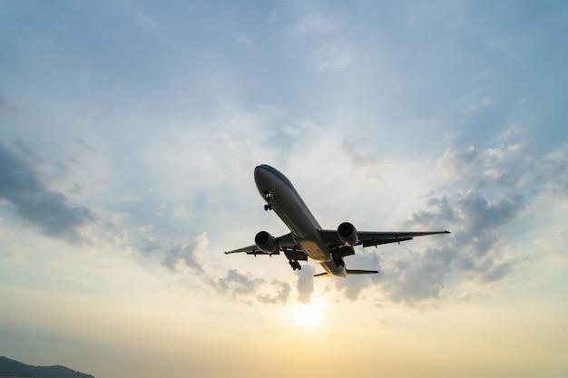 Avión está volando al aeropuerto durante la puesta de sol.