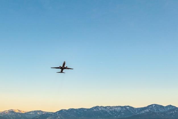 Avión volando en un cielo azul y montañas