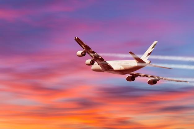 Un avión volando hacia una hermosa puesta de sol.