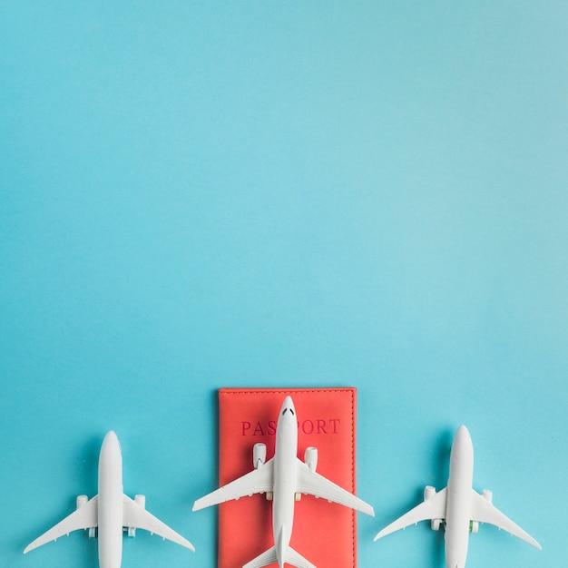 Aviones de juguete y pasaporte sobre fondo azul