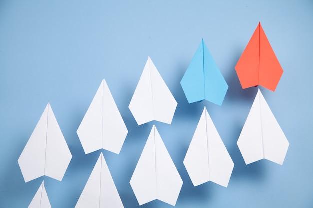 Aviones de papel rojo y blanco sobre fondo azul. liderazgo. trabajo en equipo
