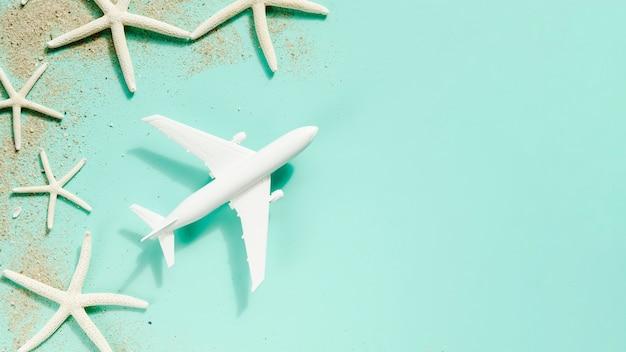 Avionito de juguete con estrellas de mar sobre mesa.