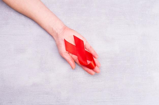 Ayuda a la cinta roja en el apoyo de la mano de la mujer para el día mundial del sida